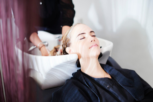 Customer with eyes closed getting hair washed in salonの写真素材 [FYI02168994]