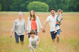 Multi-generation family holding hands and walking in rural fieldの写真素材 [FYI02168997]