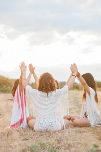 Boho women sitting in circle with arms raised and connected in rural fieldの写真素材 [FYI02168998]