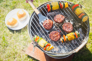Overhead view of hamburgers and vegetable skewers on barbecue grillの写真素材 [FYI02169016]