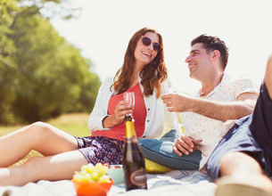 Couple drinking champagne on picnic blanket in sunny fieldの写真素材 [FYI02169043]