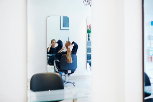 Customer with long hair looking into mirror in hair salonの写真素材 [FYI02169065]