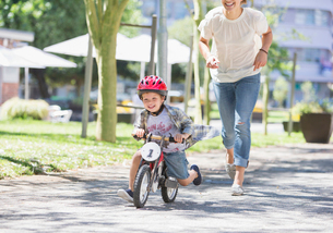 Mother chasing son riding bicycle with helmet in sunny parkの写真素材 [FYI02169074]