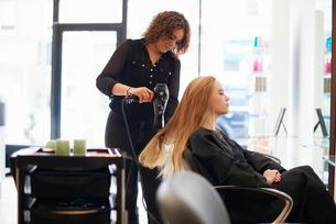 Hairdresser drying customer's long hair in salonの写真素材 [FYI02169077]