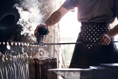 Blacksmith pouring hot liquid over wrought iron in forgeの写真素材 [FYI02169084]