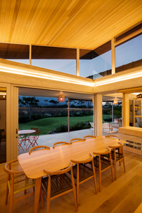 Illuminated slanted wood ceiling over long dining tableの写真素材 [FYI02169094]