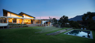 Illuminated modern house beyond yard and swimming pool at nightの写真素材 [FYI02169097]