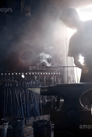 Blacksmith holding steaming wrought iron over anvil in forgeの写真素材 [FYI02169106]