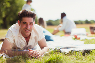 Portrait smiling man laying on picnic blanket in sunny fieldの写真素材 [FYI02169109]