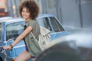 Portrait smiling woman with afro on bicycle in urban streetの写真素材 [FYI02169141]