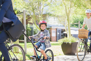 Portrait smiling boy in helmet riding tandem bicycle with father in parkの写真素材 [FYI02169162]