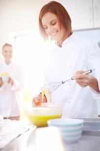 Smiling chef baking in kitchenの写真素材 [FYI02169181]