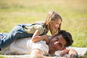 Playful daughter laying on top of father in sunny fieldの写真素材 [FYI02169187]