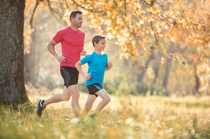 Father and son jogging in autumn parkの写真素材 [FYI02169189]