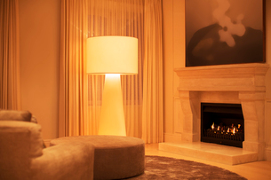 Illuminated floor lamp next to marble fireplaceの写真素材 [FYI02169205]
