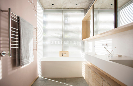 Light shining through blinds behind soaking tub in luxury bathroomの写真素材 [FYI02169258]