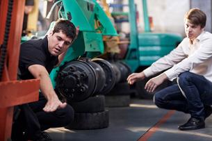 Mechanic and customer talking in auto repair shopの写真素材 [FYI02169290]