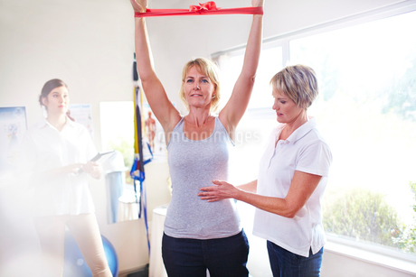 Physical therapist guiding woman pulling resistance band overheadの写真素材 [FYI02169306]