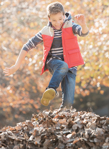 Enthusiastic boy jumping over pile of autumn leavesの写真素材 [FYI02169357]