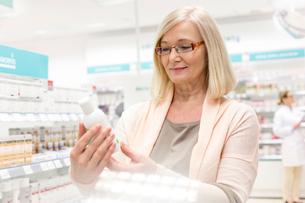 Customer reading label on bottle in pharmacyの写真素材 [FYI02169410]