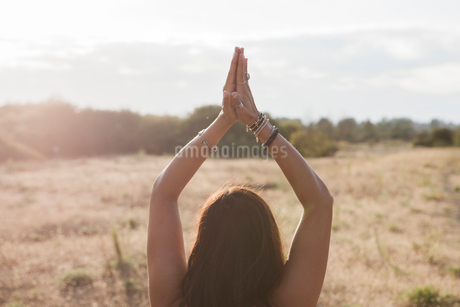 Woman meditating with hands clasped overhead in sunny rural fieldの写真素材 [FYI02169432]