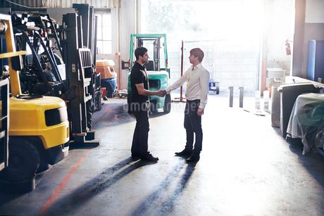 Mechanic and customer handshaking in auto repair shopの写真素材 [FYI02169444]