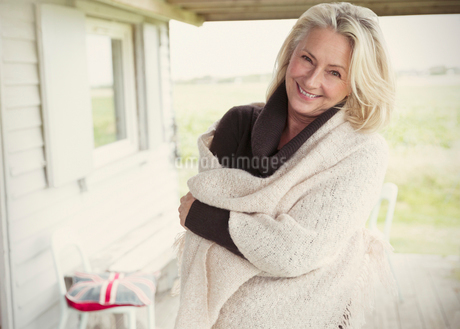 Portrait smiling senior woman wearing shawl on porchの写真素材 [FYI02169460]