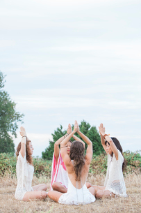 Boho women meditating with hands clasped overhead in circle in rural fieldの写真素材 [FYI02169467]