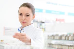 Pharmacist reading label on box in pharmacyの写真素材 [FYI02169475]