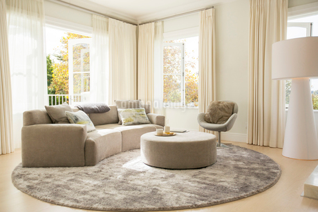 Round carpet under sofa and ottoman in living roomの写真素材 [FYI02169488]