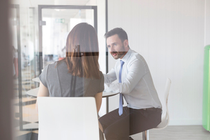 Businessman and businesswoman talking in officeの写真素材 [FYI02169541]