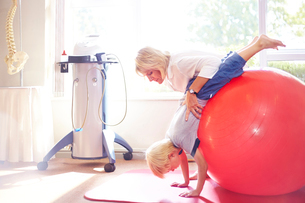 Physical therapist holding boy over large fitness ballの写真素材 [FYI02169550]