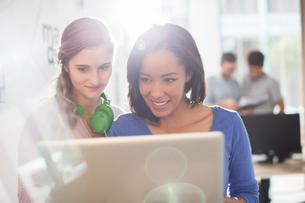 Creative businesswomen with headphones using digital tabletの写真素材 [FYI02169551]