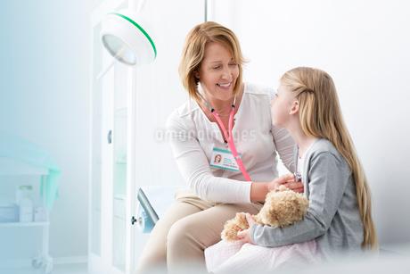 Pediatrician using stethoscope on girl patient in examination roomの写真素材 [FYI02169584]