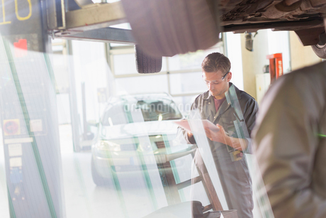 Mechanic with clipboard under car in auto repair shopの写真素材 [FYI02169611]