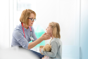 Pediatrician checking girl patient's glands in examination roomの写真素材 [FYI02169648]