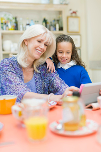 Grandmother and granddaughter using digital tablet at breakfast tableの写真素材 [FYI02169657]