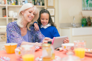 Grandmother and granddaughter using digital tablet at breakfast tableの写真素材 [FYI02169757]
