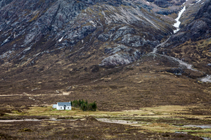 House in remote valley below craggy mountains, Glencoe, Scotlandの写真素材 [FYI02169766]