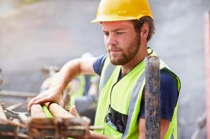 Construction worker lifting rebarの写真素材 [FYI02169771]