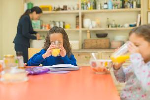 Girls drinking orange juice at breakfast tableの写真素材 [FYI02169795]