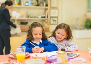 Girls doing homework at breakfast tableの写真素材 [FYI02169804]