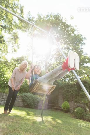 Grandmother pushing carefree granddaughter on swing in backyardの写真素材 [FYI02169815]