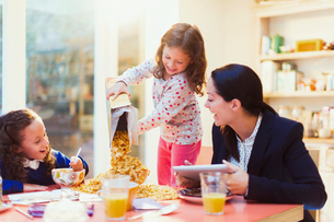 Girl pouring abundance of cereal at breakfast tableの写真素材 [FYI02169816]