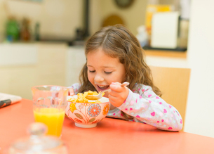 Girl eating cereal at breakfast tableの写真素材 [FYI02169850]