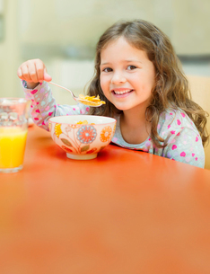 Portrait smiling girl eating cereal at breakfast tableの写真素材 [FYI02169877]