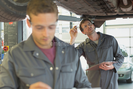 Mechanic with clipboard working under car in auto repair shopの写真素材 [FYI02169891]