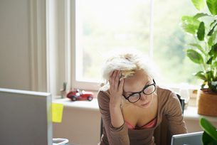 Stressed woman with hands in hair working in officeの写真素材 [FYI02169894]