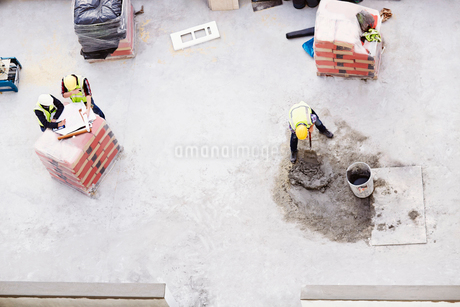 Overhead view of construction workers laying concrete at construction siteの写真素材 [FYI02169896]