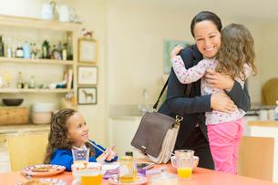 Working mother hugging daughter goodbye at breakfast tableの写真素材 [FYI02169957]